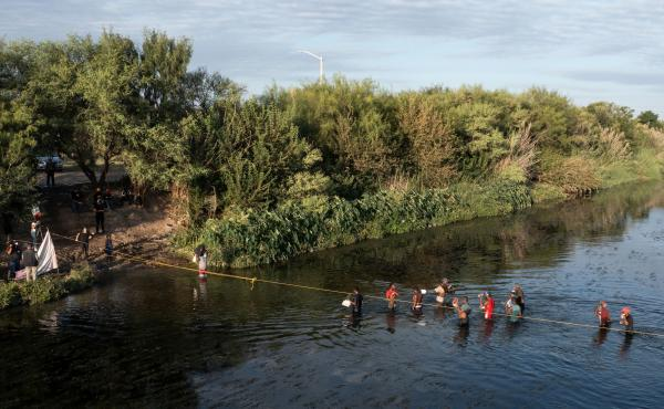 Haitian migrants cross the Rio Grande on Wednesday to get food and water in Mexico, as seen from Ciudad Acuña, Mexico. The U.S. is allowing some migrants to enter the country and sending others back to Haiti.