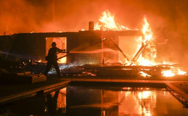 A firefighter battles the Woolsey Fire burning a home in Malibu, Calif. in November. Fire scientists are finding that homes most frequently burn from flying embers after the initial blaze has passed through.