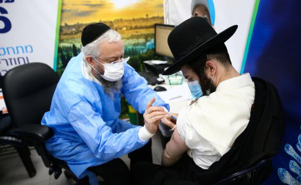 An Ultra-Orthodox Jewish man receives a dose of the Pfizer-BioNtech vaccine in the Israeli city of Bnei Brak in February.