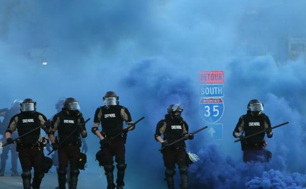 Police advance on demonstrators who are protesting the killing of George Floyd on Saturday in Minneapolis.