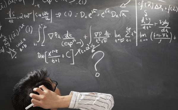Looking at difficult mathematics equations on a blackboard.