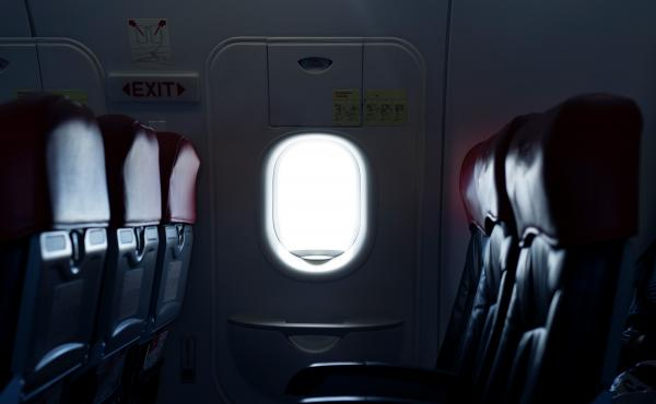 Where should you sit on a plane to reduce the risk of exposure to germs spread by infectious passengers?