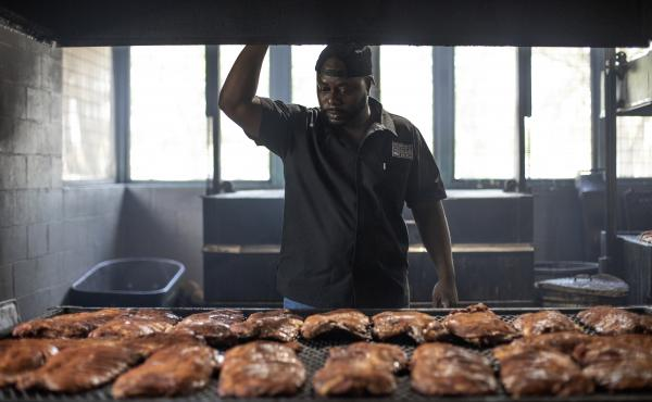Rodney Scott checks racks of ribs as they cook on July 3, 2018 in Charleston, S.C.
