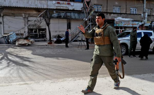 A security force member walks outside a shuttered restaurant Thursday in Manbij, Syria, the site of a suicide attack that killed more than a dozen people, including four Americans, a day earlier. The Islamic State claimed responsibility for the attack.