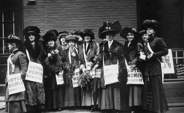 Members of the women's suffrage movement prepare to march on New York's Wall Street in 1913, armed with leaflets and slogans demanding the vote for women.