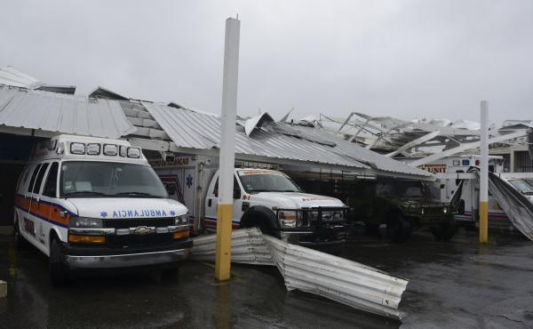 Rescue vehicles stand trapped under a collapsed awning while Hurricane Maria lashed Humacao, Puerto Rico on Wednesday.