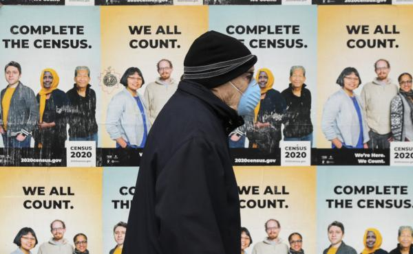 A person wearing a mask walks past posters encouraging census participation in Seattle in April 2020. The coronavirus pandemic has disrupted not only last year's national head count, but also a critical follow-up survey that the U.S. Census Bureau relies