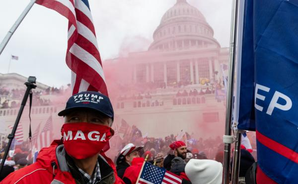 A protester unleashes a smoke grenade in front of the U.S. Capitol building on Jan. 6, 2021.