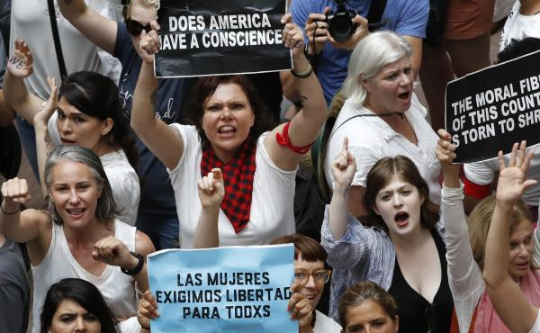 Women hold signs as they protest the separation of immigrant families inside the Hart Senate Office Building on Capitol Hill in Washington.