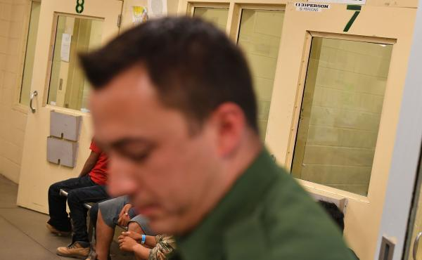In this file photo, young migrants, whose faces cannot be shown, sit inside a U.S. Customs and Border Protection Facility in Tucson, Arizona.