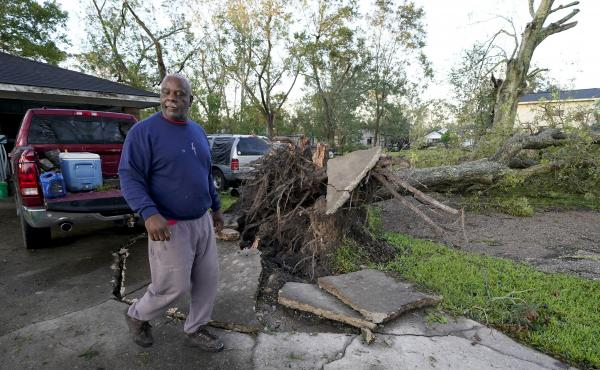 Marcus Peterson walks past a downed tree in his yard in Jennings, La., after Hurricane Delta moved through the region. Delta hit as a Category 2 hurricane with top winds of 100 mph before rapidly weakening over land.