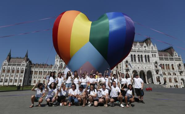 Activists pose for a photo after raising a large rainbow heart in front of Hungary's parliament building in Budapest on Thursday. The activists are protesting against a new law they say discriminates against and marginalizes LGBTQ people.