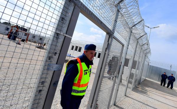 """A police officer walks through a gate at the Tompa border station transit zone in April 2017. Hungary has two """"transit zones"""" with shipping containers that are used to automatically detain migrants while their asylum claims are investigated. This month, H"""
