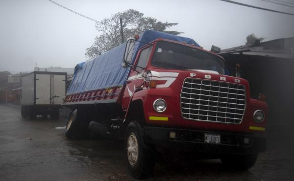 A truck flounders in a flooded street in Puerto Cabezas, Nicaragua, just hours before Hurricane Iota made landfall in the country Monday night. By Tuesday morning, the storm had significantly weakened, but it still poses life-threatening dangers for resid
