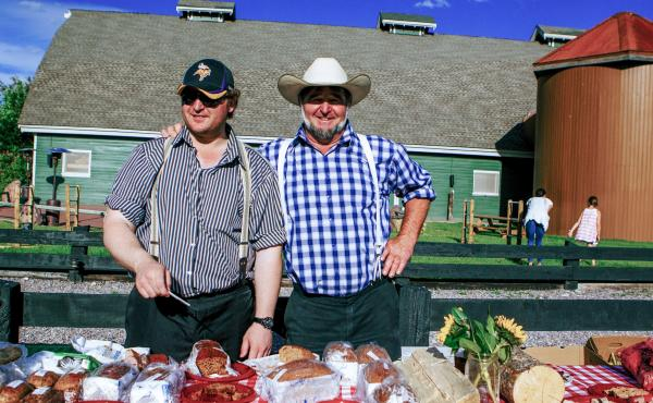 Brian Kleinsasser, left, who works in the hog barn at Cool Spring Colony, helps Jake Waldner set up the Hutterite table during a Long Table dinner event at The Resort at Paws Up.