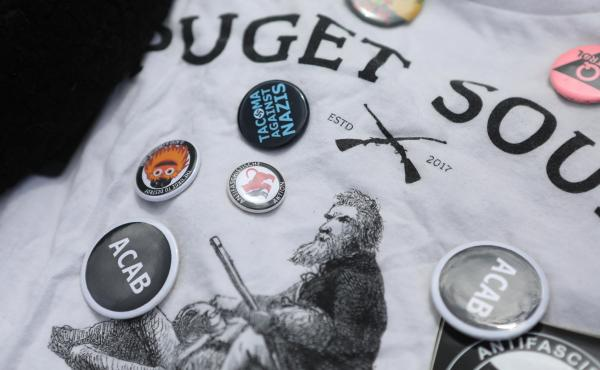 """A shirt and pins that belonged to  van Spronsen. He stood up to far-right leaders at local rallies, and he was a fixture at demonstrations against U.S. immigration policies, especially family separation. """"Kids in cages,"""" he called it."""