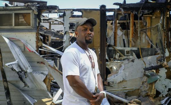 Trevon Ellis, owner of the Fade Factory, stands in front of the building where his barbershop was destroyed in Minneapolis. Sometime late Saturday someone broke into the shop and lit it on fire.