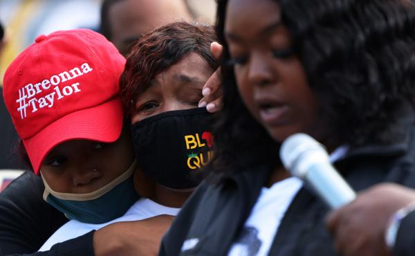 """""""You didn't just rob me and my family, you robbed the world of a queen,"""" Breonna Taylor's mother, Tamika Palmer, said in a statement read aloud Friday by Palmer's sister, Bianca Austin. In this photo, Ju'Niyah Palmer is seen wiping away tears from her mot"""