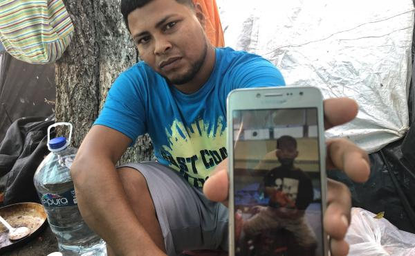 Migrant parents in the tent camps in Matamoros, Mexico, are sending their kids across the border and taking advantage of the rule that unaccompanied children can't be returned to Mexico. Here,  Alexis Martinez holds a cellphone photo of his 7-year-old son