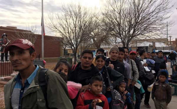Recently released from ICE custody, migrants form a line to board a bus that will take them to a shelter on Christmas Day.