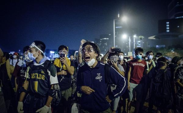 Pro-democracy protesters shout at police forces outside the central government offices in Hong Kong.