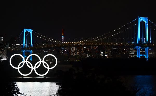 """""""We shall all need to make sacrifices and compromises"""" to put on the Tokyo 2020 Olympics, IOC President Thomas Bach says, announcing funding to help keep the delayed games on track. The Olympic rings, the Rainbow Bridge and the Tokyo Tower are seen in Tok"""