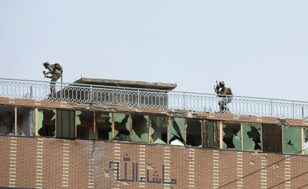 Afghan security personnel take position on the top of a building where insurgents were hiding in the city of Jalalabad, Afghanistan, on Monday. The day before, militants attacked a prison holding many ISIS members.