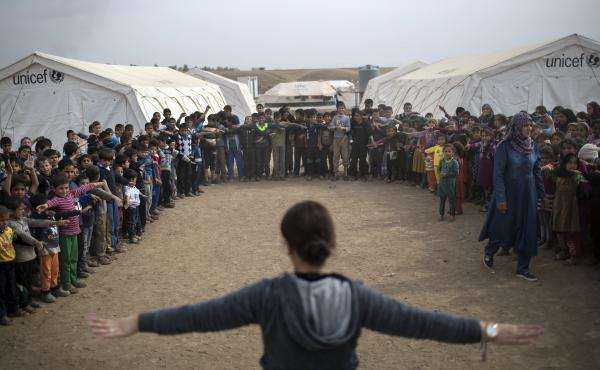 Iraqi children who were displaced by fighting in Mosul follow instructions given by a teacher, center, during an outdoor class at a camp for internally displaced people in Hassan Sham on Nov. 10.