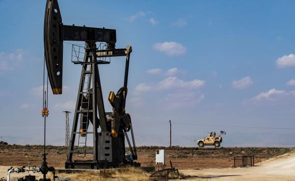 A U.S. military vehicle drives past an oil pump jack in the countryside of Syria's northeastern city of Qamishli. President Trump is leaving some U.S. troops in Syria, with the goal of controlling Syria's oil fields. But legal experts say exploiting the o