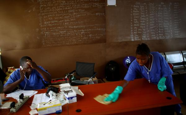 """The health workers of Sierra Leone — like Dr. Komba Songu M'Briwah (on the phone) — were dedicated to fighting Ebola. But they had a huge handicap. A government report reveals that some of the money allocated went to pay """"ghost workers."""""""