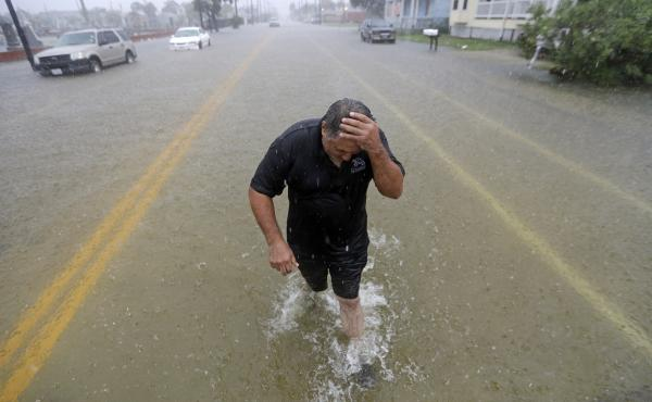 Parts of eastern Texas could see nearly 3 feet of rain through Friday, forecasters say, warning of potential flash floods from Tropical Depression Imelda. Here, Angel Marshman walks through floodwaters in Galveston after trying to start his flooded car We
