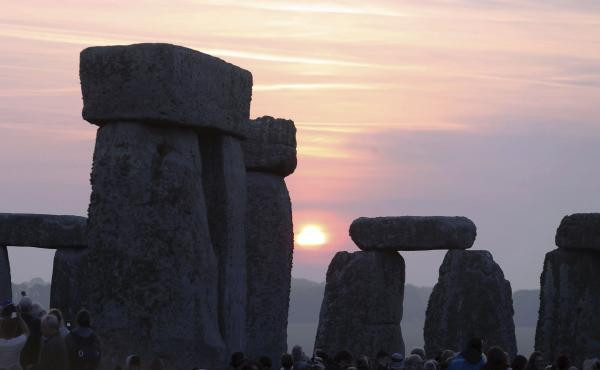 Thousands of people stand among the ancient stones at Stonehenge in Salisbury, England, at sunrise on the summer solstice. Archaeologists on Monday announced the discovery of a ring of shafts about 2 miles away.