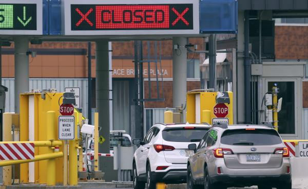 "Vehicles wait in line to cross into Canada at the Peace Bridge Plaza on March 18, 2020, in Buffalo N.Y. The Canada-U.S. border will be closed to non-essential traffic in both directions ""by mutual consent,"" President Donald Trump confirmed Wednesday, as e"