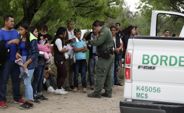 A Border Patrol agent checks the names and documents of families who crossed the nearby U.S.-Mexico border near McAllen, Texas. Immigration authorities say they expect the continuing surge of Central American families crossing the border to multiply in th