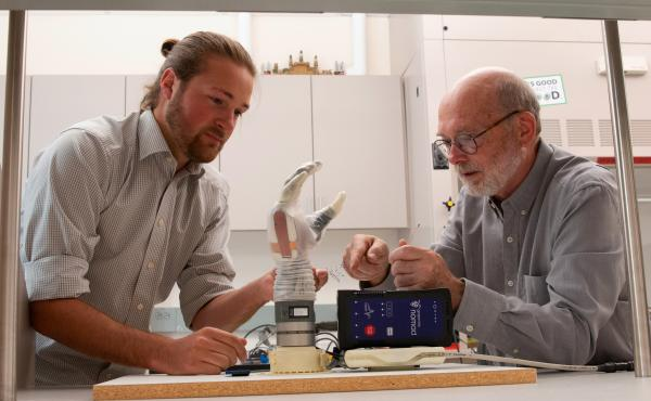 University of Utah doctoral student Jacob George, left, and associate professor Greg Clark examine the LUKE arm that they use for their experiments. A man who lost his lower arm in an electrical accident was able to experience some sense of touch and fine
