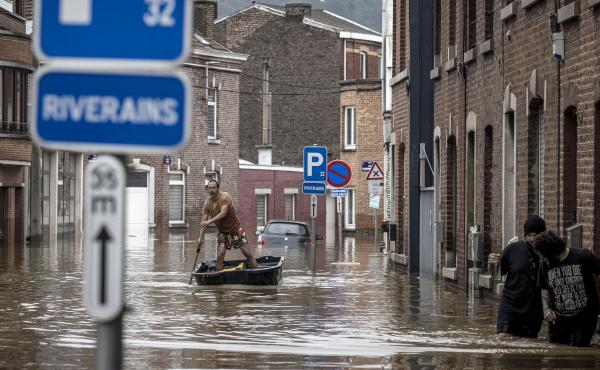 A man rows a boat down a residential street after flooding in Liège, Belgium, on Friday.