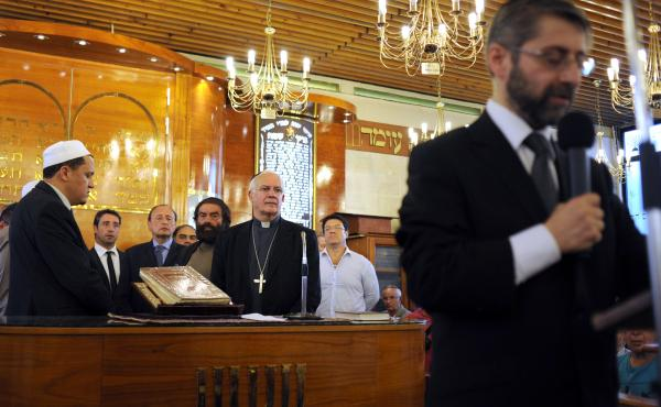 Great Rabbi of France Haim Korsia, right, speaks as the Imam of the eastern suburb of Drancy, Hassen Chalghoumi, left, and others listen during a ceremony at the synagogue of Sarcelles, France, in July 2014, after pro-Palestinian protests in Paris and Sar