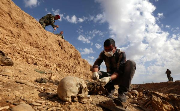 An Iraqi man inspects the remains of what are believed to be members of the Yazidi minority, in the northern village of Sinuni on Feb. 3.