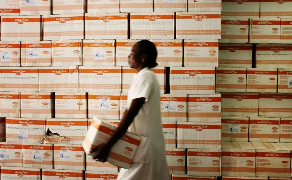 A nutritionist fetches a carton of Plumpy'Nut for malnourished patients at a hospital in Burkina Faso.