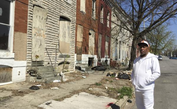Marvin Cheatham, president of the Matthew Henson Neighborhood Association, stands in front of a row of abandoned homes in West Baltimore. He would like to see them torn down and replaced by a food market, a senior center and a health clinic — all of whi