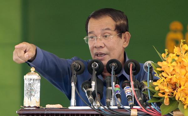 Cambodia's Prime Minister Hun Sen speaks to garment workers during a visit to a factory outside Phnom Penh on Aug. 30. His government has slapped the English-language Cambodia Daily with a $6.3 million tax bill and ordered it to pay by Sept. 4. If it does
