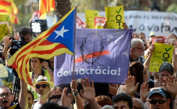 People hold Catalan pro-independence flags outside the high court in Barcelona, Spain, on Thursday. After a daylong protest that lasted well into the night, several thousand independence supporters gathered again in front of the high court in what influen