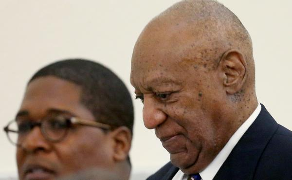 Bill Cosby walks through the Montgomery County Courthouse in Norristown, Pa., with his spokesman, Andrew Wyatt, during a break in his sexual assault retrial on Tuesday.