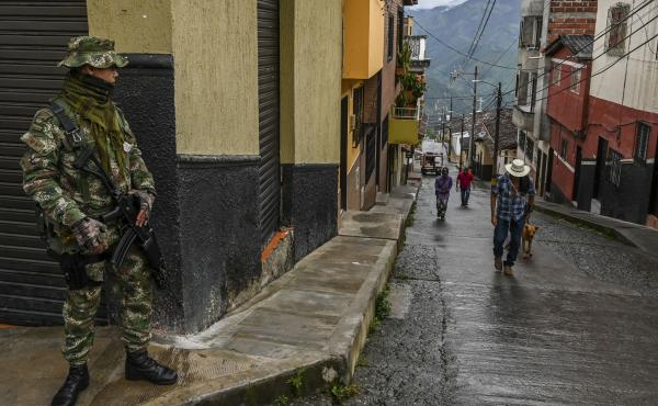 A soldier stands guard on a street in Ituango, Colombia, on Oct. 19, 2019. The town is home to a new public radio station staffed by ex-FARC rebels and war victims. Reporters often conduct interviews with former combatants and update listeners on the prog