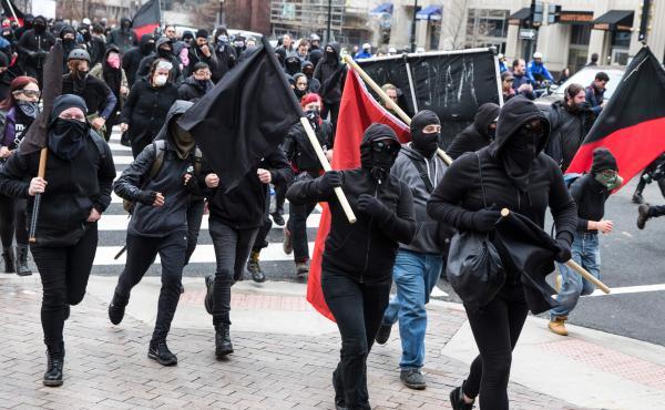 Protestors run through the street before the inauguration of Donald Trump.