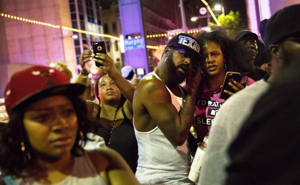 Protesters react as police officers arrest a bystander in downtown Dallas following Thursday's shooting.