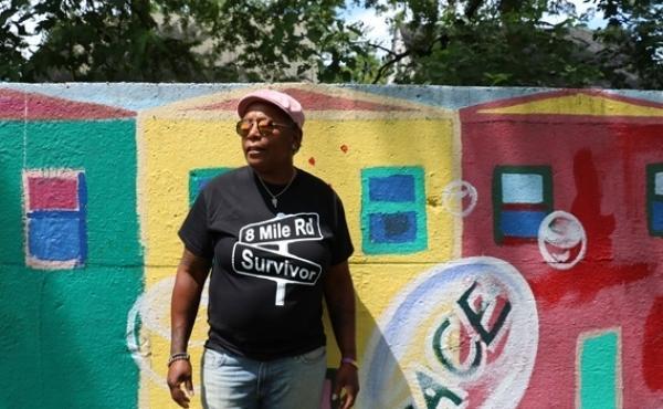 """Detroit resident Teresa Moore, who has lived in the city's 8 Mile Road neighborhood for 59 years, stands in front of what she calls a """"segregation wall."""""""