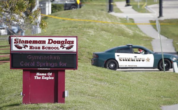 Law enforcement officers block off the entrance to Marjory Stoneman Douglas High School on Feb. 15 in Parkland, Fla. A day earlier a gunman opened fire in the school.