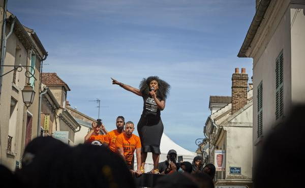 "Assa Traoré addresses a crowd during a demonstration in Persan, France, to commemorate the fourth anniversary of her brother Adama Traoré's death. ""The fight for justice for Adama belongs to all of France,"" she says."