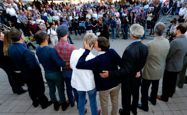 Kody Partridge (center right) and her partner, Lauri Wood, kiss at a same-sex marriage celebration Monday in Salt Lake City. The status of gay marriage remains uncertain in Kansas and Wyoming, where officials say no court has ruled on their ban specifical